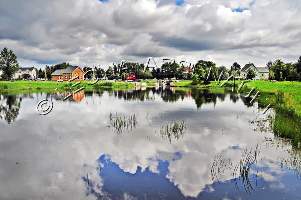 CANADA;PRINCE EDWARD ISLAND;PRINCE COUNTY;WELLINGTON;WATER;PONDS;CLOUDS;REFLECTIONS;BUILDINGS;HOUSES;SUMMER;WATERSCAPE;HORIZONTAL